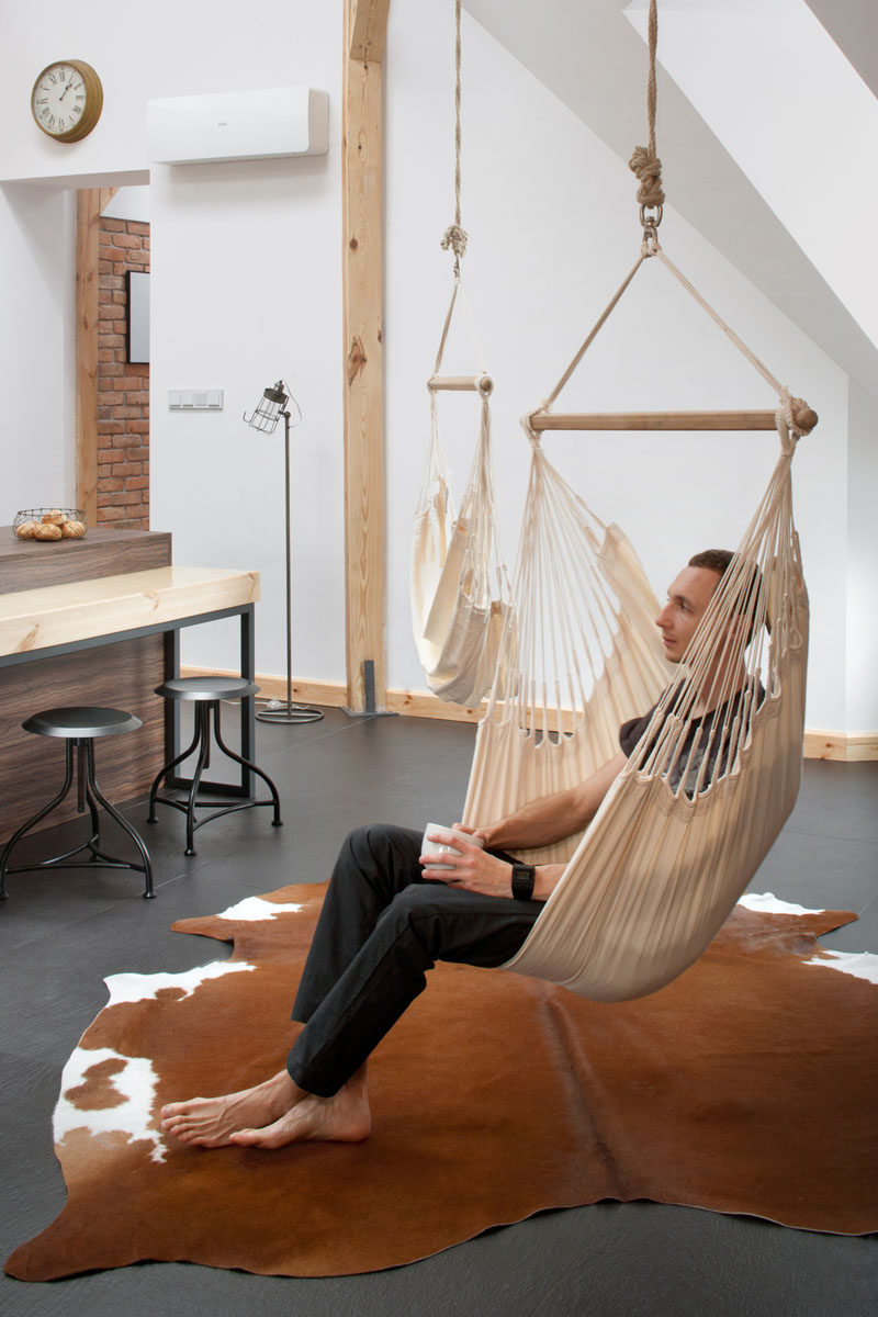This renovated loft has a couple of hammock chairs hanging from the ceiling.