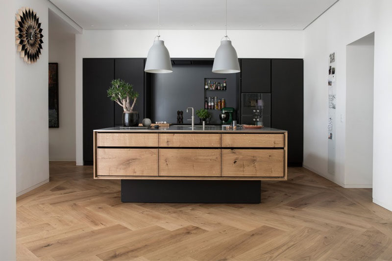 16 Inspirational Pictures Of Herringbone Floors // The herringbone wood floors and wood elements in the island keep this kitchen feeling natural and bright even with the all black cabinetry.