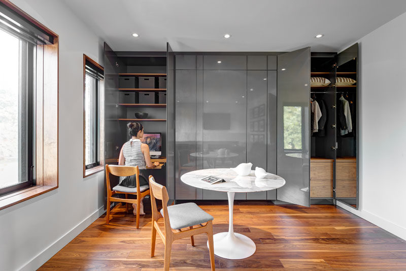 This guest bedroom has been set up as an office with a wall full of cabinetry that provides plenty of storage to the room and hides a small work desk.