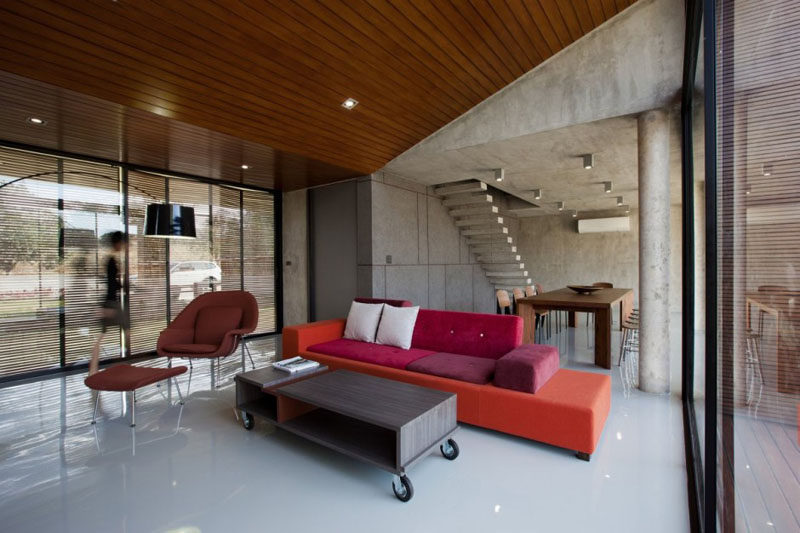 Wood and brightly colored furniture soften up the interior of this concrete home.
