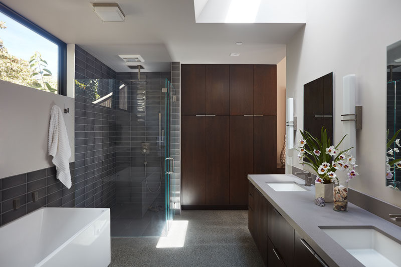 In this master bathroom, there's plenty of light from the window and skylight, and the shower has been separated from the bath, although they do share the same gray subway tile.