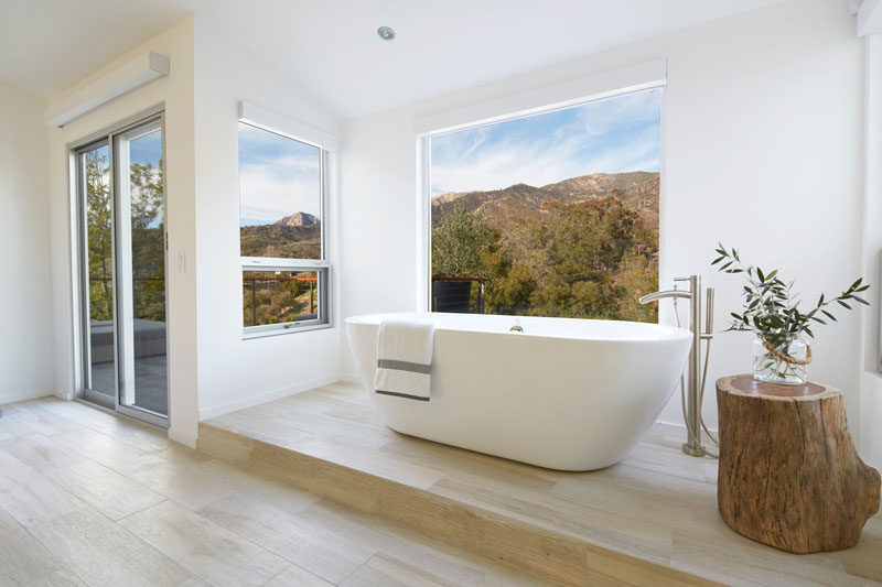 This master bathroom features a freestanding bathtub raised up onto a platform so that whoever is in the bath can easily enjoy the picturesque views of the surrounding landscape.