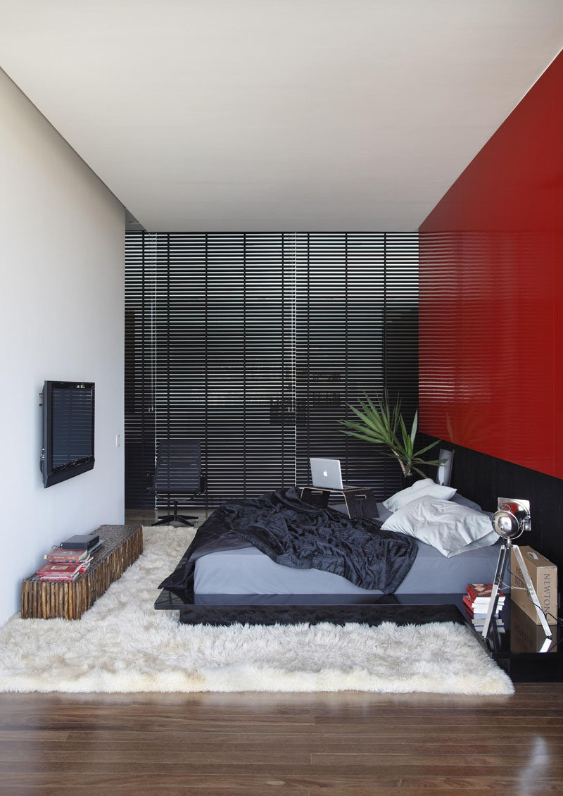 A bright red feature wall stands out in this otherwise black and white bedroom.