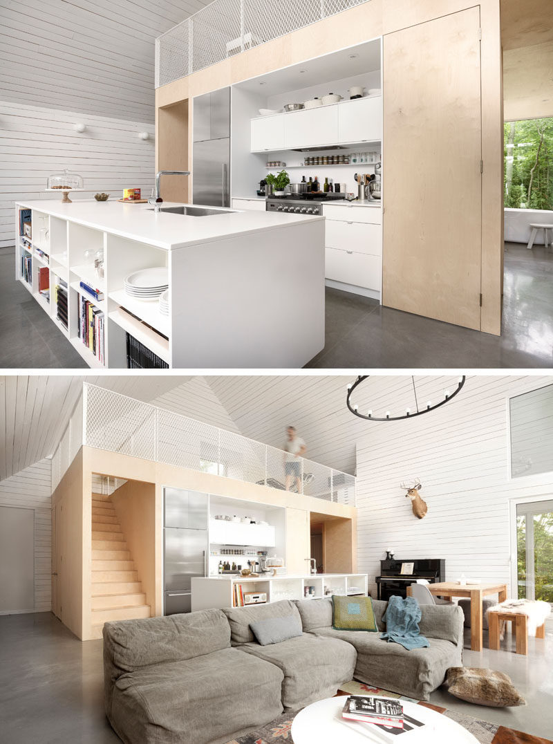 In this chalet, the kitchen has a large white island with shelving on one side, ideal for storing books and games. Above the kitchen is a loft with additional living space.