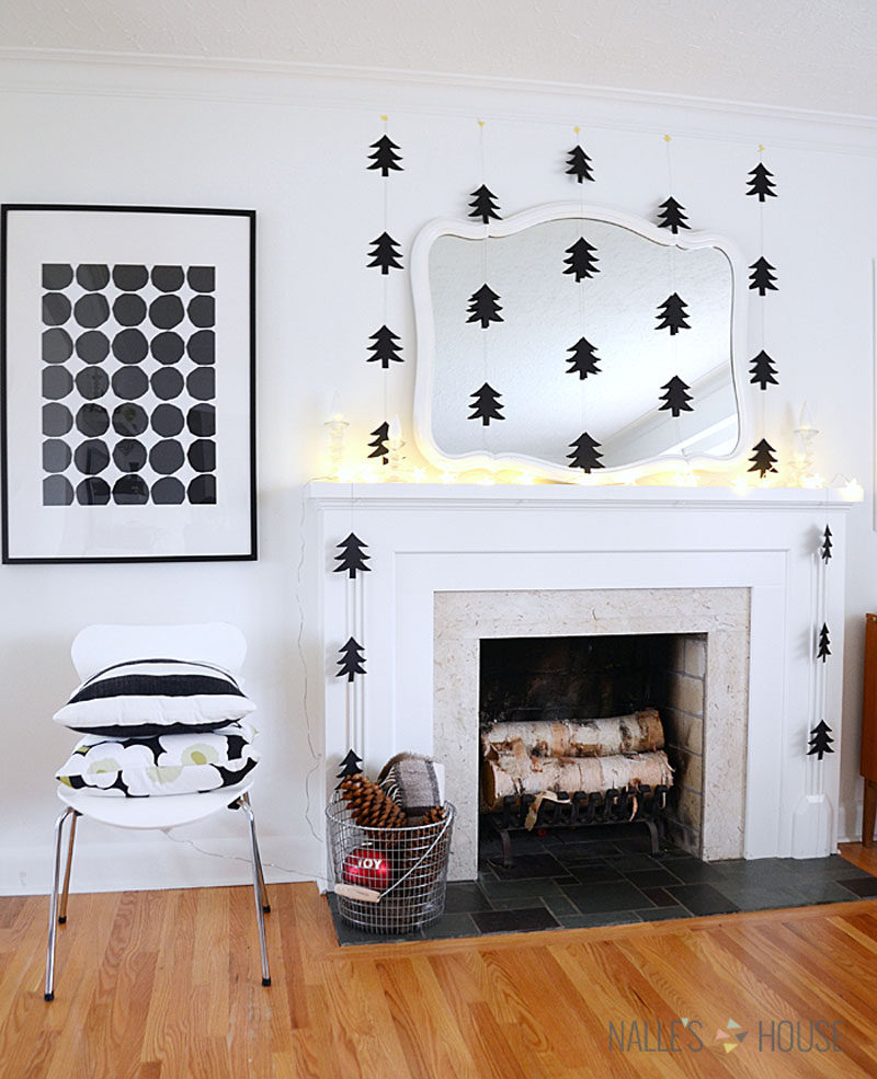 30 Modern Christmas Decor Ideas For Your Home // Black paper tree cut outs hanging from the ceiling frame the fireplace and make the room feel more cozy.