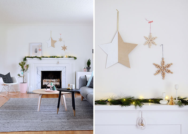 30 Modern Christmas Decor Ideas For Your Home // A simple garland of natural greenery and twinkle lights and the wooden decorations above the mantle keep this bright living room feeling welcoming yet cozy.