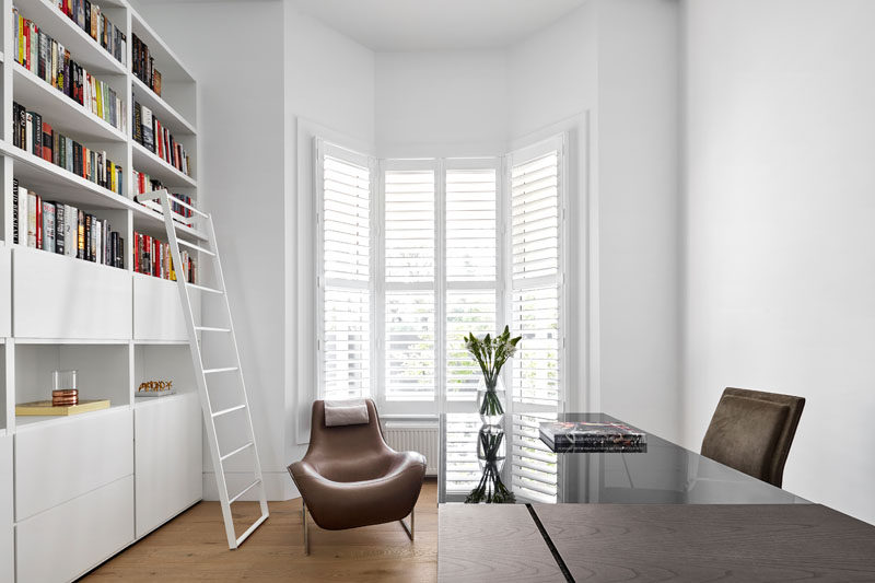 This bright white home office has shelving running along one wall with a bay window providing lots of natural light.