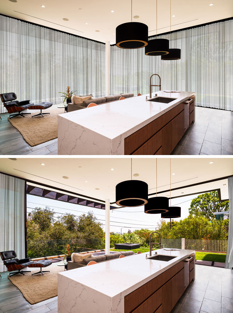 This kitchen and living room open up to a grassy area.