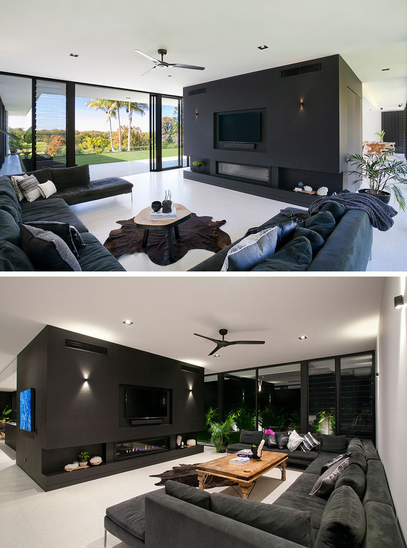 This modern living room is open to the backyard of this home. A large sofa focused on the tv and fireplace makes it the ideal place to watch movies.