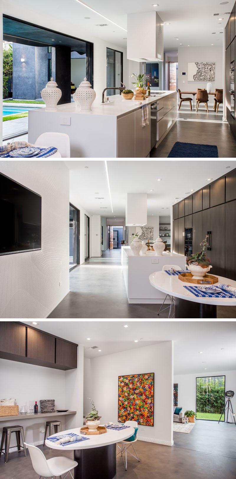 In this modern kitchen, the white kitchen island is a bright contrast to the wall of dark cabinetry behind it. There's also an additional smaller dining area at the end of the kitchen.