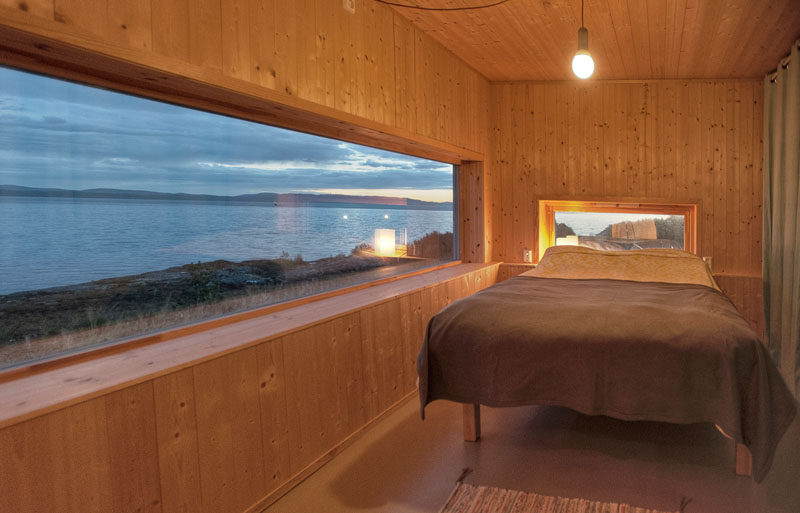 In this small wooden cabin in Norway there are lots of windows that perfectly frame the water views.