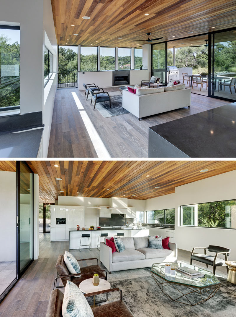 In this house, the wooden ceiling outside carries on through to the interior of the home. The living room is surrounded by glass, and behind the living room is the kitchen.