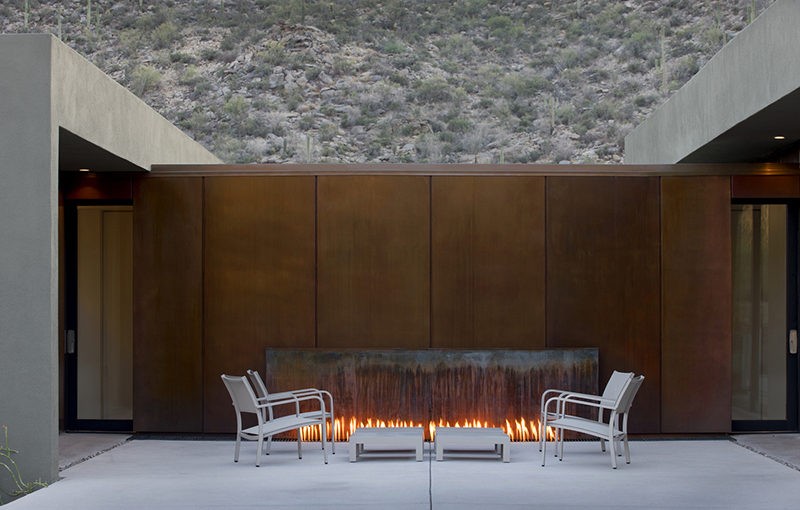 This outdoor fireplace is surrounded by weathering steel, and is located between two different areas of the home.