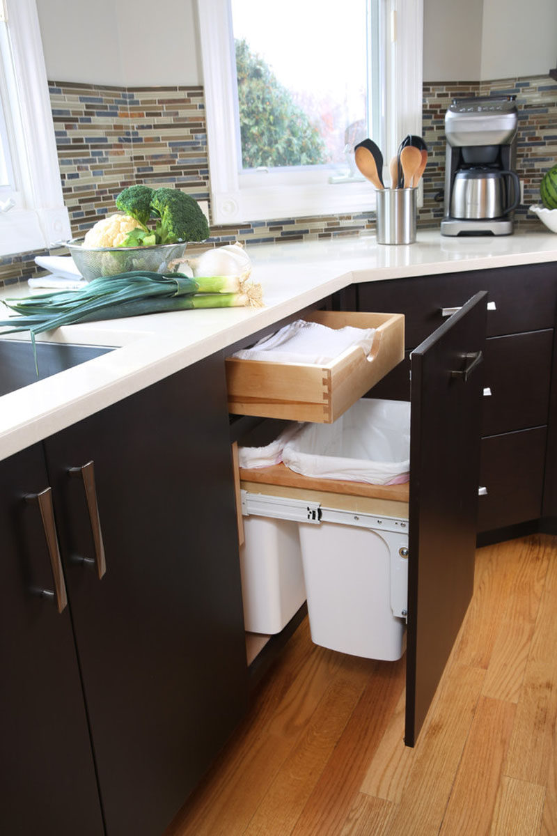 Kitchen Design Idea - Hide Pull Out Trash Bins In Your Cabinetry // The pull out trash bins in this kitchen also hang but are lower down to accommodate a drawer that sits above them.