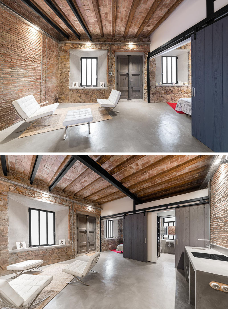 In this renovated workshop, the guest suite / studio space shows off original details like the walls and ceiling, while new details like a concrete floor, barn doors and a bathroom have been included.