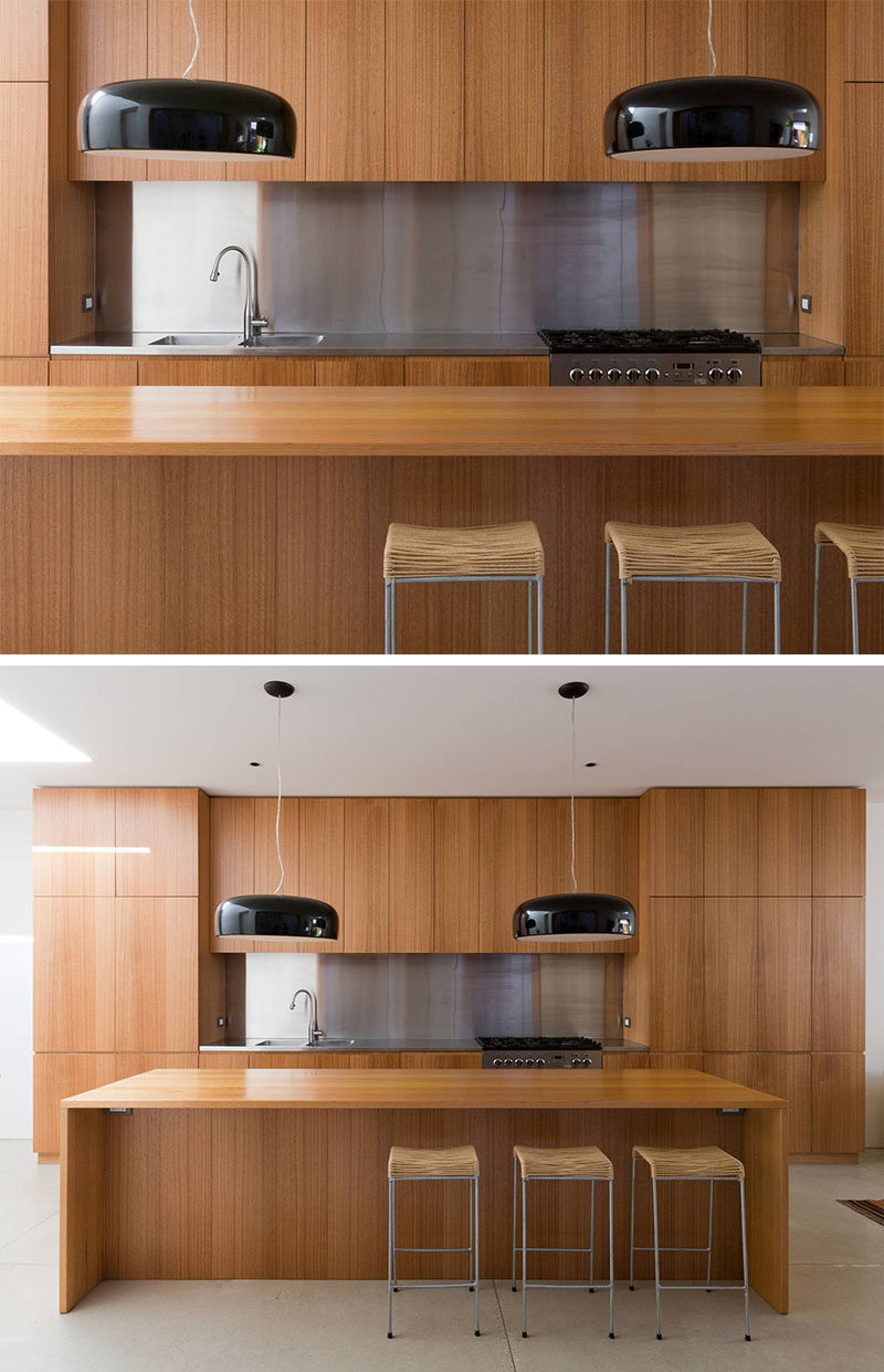 Kitchen Design Idea - Stainless Steel Backsplash // The modern stainless steel work top and backsplash contrast the natural look of the wood cabinetry and island in this kitchen.