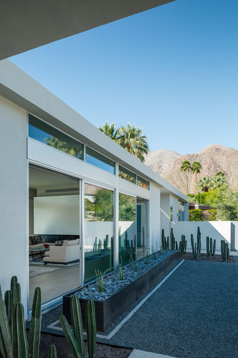 A large steel planter filled with cacti is featured at the front of this Californian home.