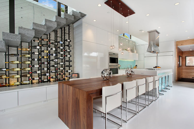 Wine Rack Ideas - Show Off Your Bottles With A Wall Mounted Display // This wine display under the stairs holds lots of bottles and is lit up from the bottom to put emphasis on the shapes of the bottles and the styles of the labels.