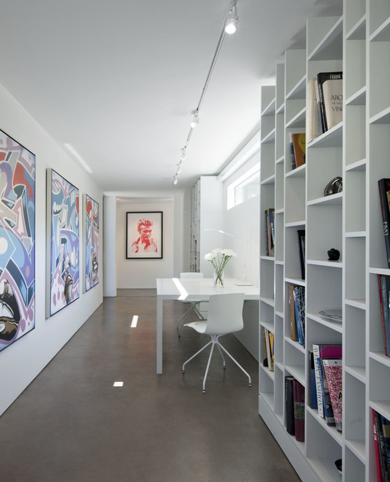 This bright white hallway, also known as the home's library, is filled with colorful artwork, floor-to-ceiling bookshelves, and a small desk area.