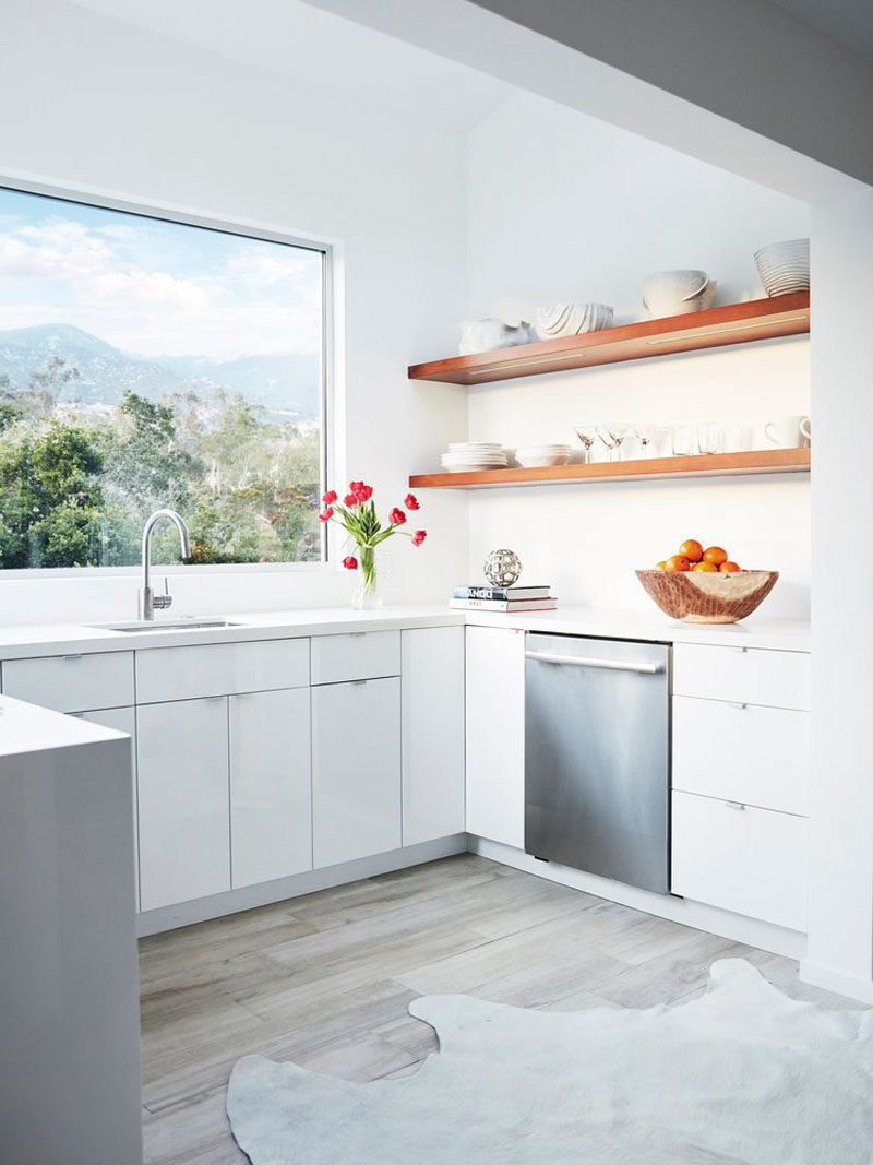 In this kitchen, a large picture window perfectly frames the view of the mountains and open wood shelving lets you display your favorite serving items.