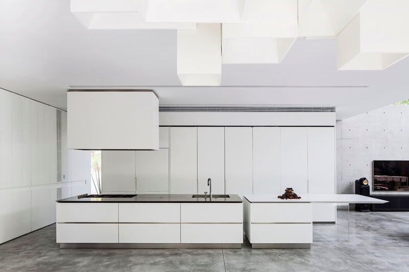 The Use Of White Cabinets And Concrete Floors Give This Kitchen A Modern Look