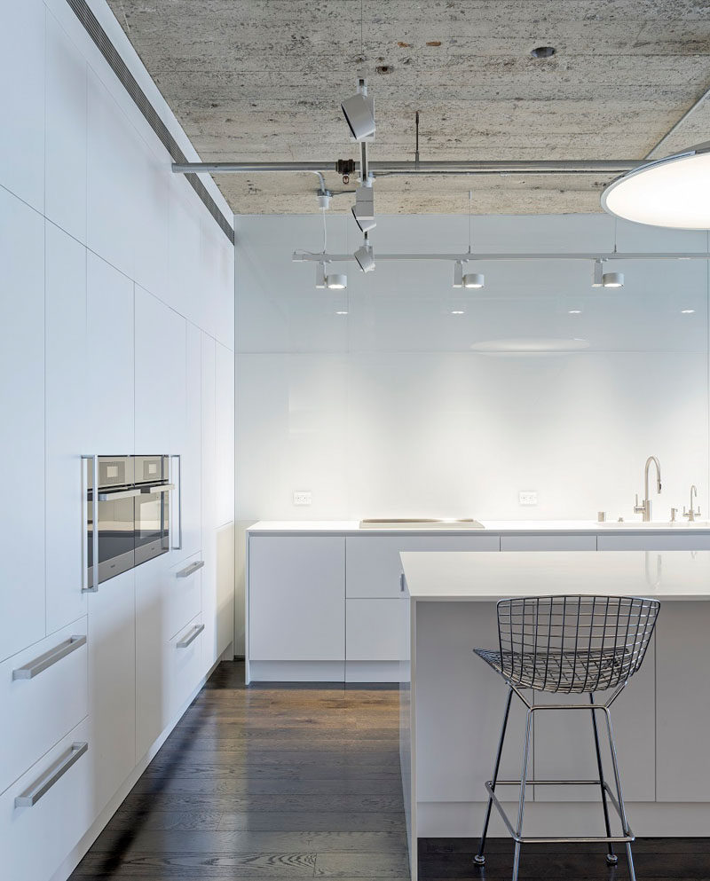 Kitchen Design Ideas - White, Modern and Minimalist Cabinets // The walls of white cabinetry contrast the concrete in this apartment and makes for a minimalist feel throughout.