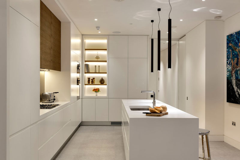 Kitchen Design Ideas - White, Modern and Minimalist Cabinets // Warm wood above the stove, and soft lighting creates a cozier feel in this kitchen with all white cabinetry.