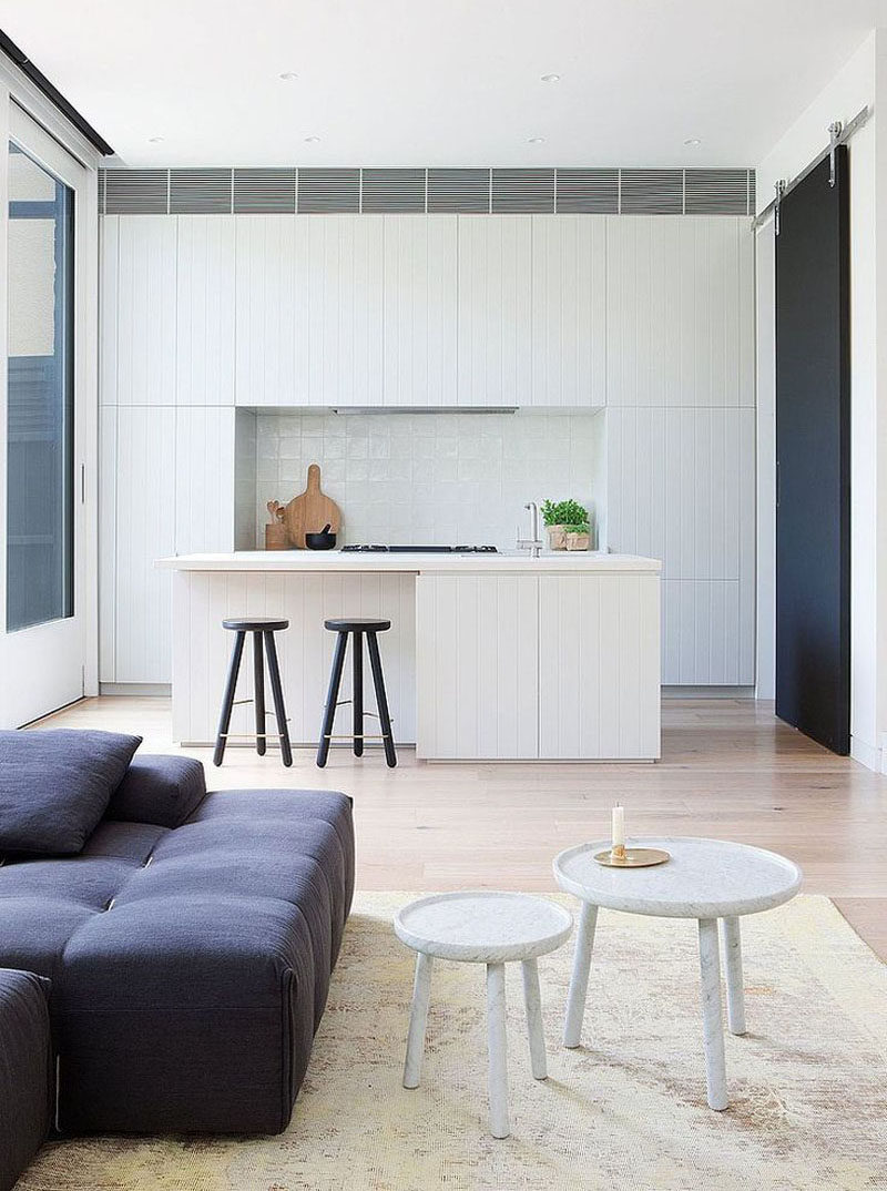 Kitchen Design Ideas - White, Modern and Minimalist Cabinets // A few black details, including the stools, the stove, and the sliding barn door, interrupt the all white cabinetry in this modern kitchen.
