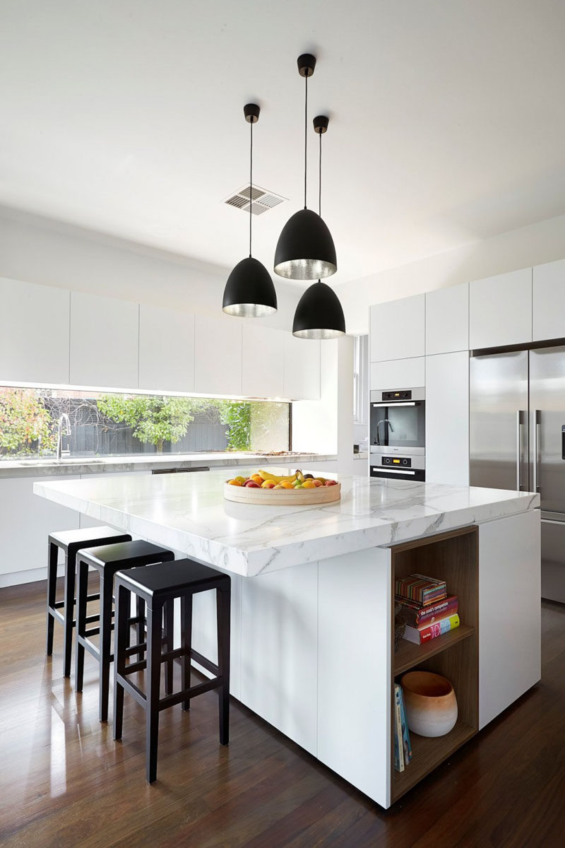 The white cabinets stainless steel appliances and marble countertops give this kitchen a super modern feel while the wood floors keep it feeling warm and