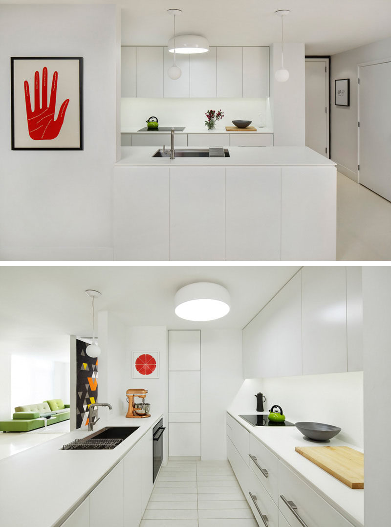 Kitchen Design Ideas - White, Modern and Minimalist Cabinets // The white cabinetry in this kitchen is only broken up by the black appliances and small decorative elements like the green kettle and red art piece.