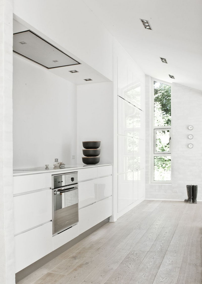 Kitchen Design Ideas - White, Modern and Minimalist Cabinets // The white cabinetry of this kitchen and the light wood floor give the space an extremely bright look that's amplified by the natural light coming through the windows.