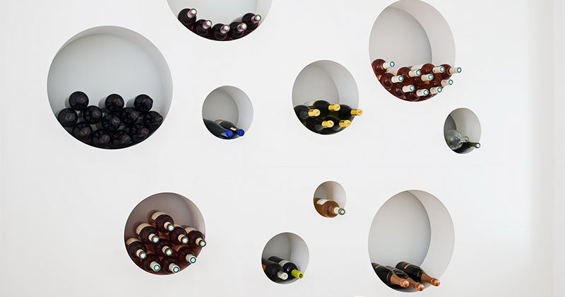 Wine Storage Idea ? This wall of circular cut-outs is a creative way to rack up the bottles