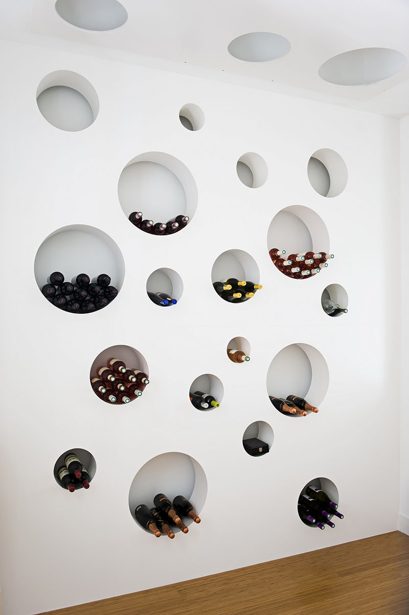 This cellar features a wall with circular cut outs to store the wine bottles.