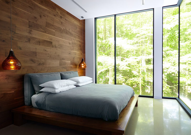 This bedroom has a feature wall and bedframe made from wood.
