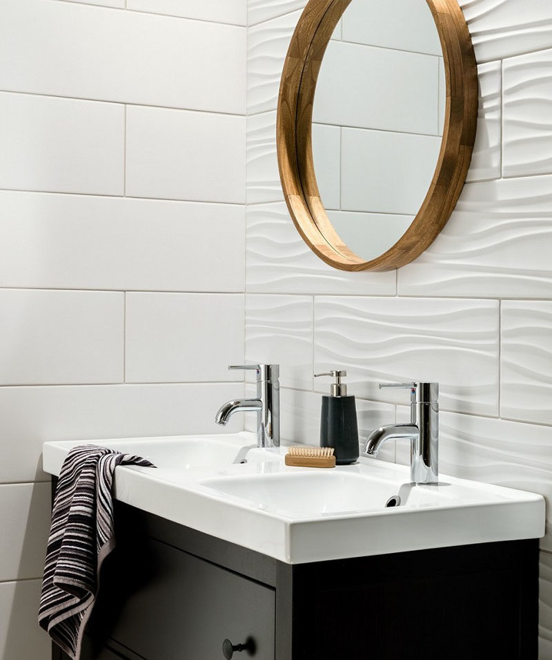 the ripples in these white bathroom tiles used on one wall add a wavelike look to the wall but are close enough to the style of the flat tiles to make