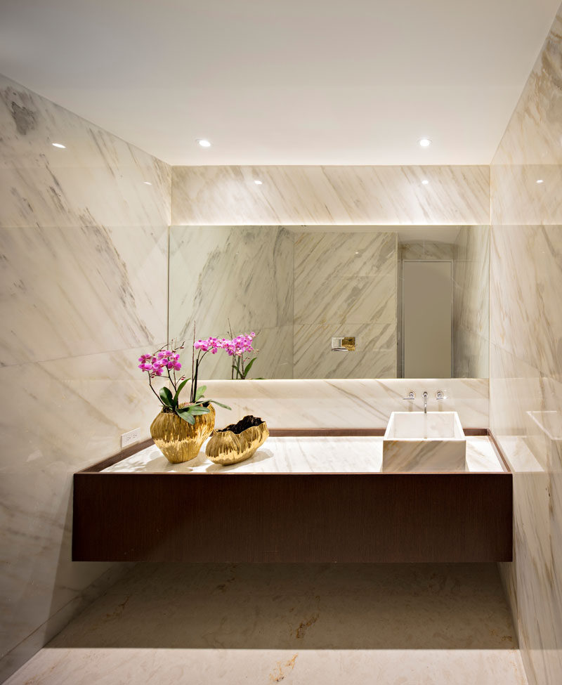 In this bathroom, stone covers the walls and a back-lit mirror creates soft ambient lighting.