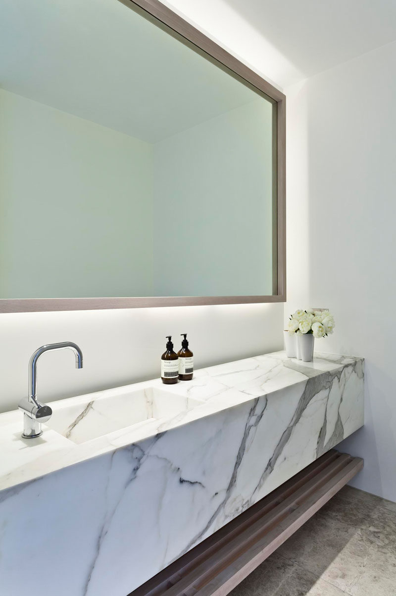 This modern bathroom has a backlit mirror, a marble vanity and an open wooden shelf for additional storage.