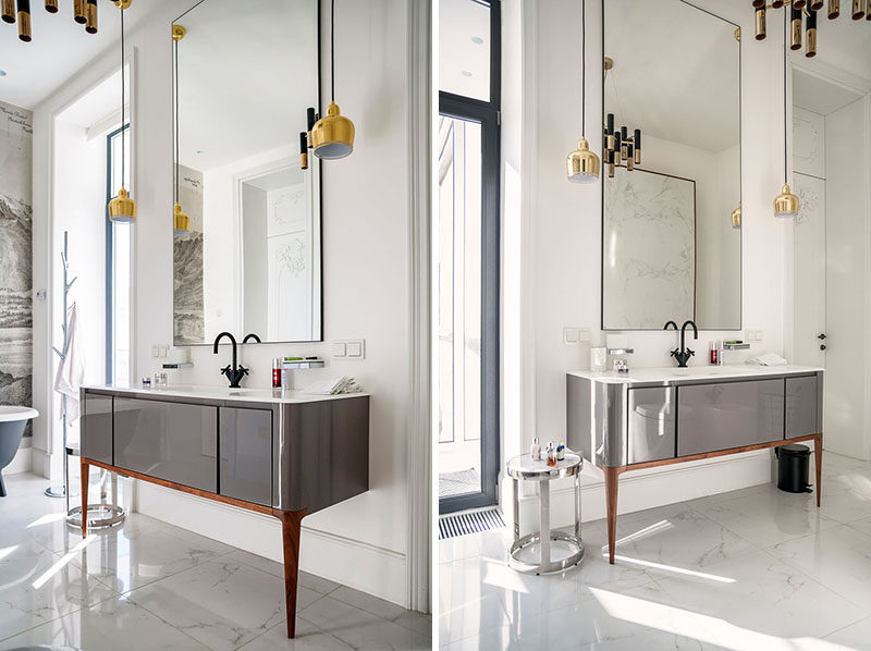 In this bathroom, a vanity with sleek grey cabinetry and only two legs is attached to wall. A tall mirror helps the space to feel even larger than it is.
