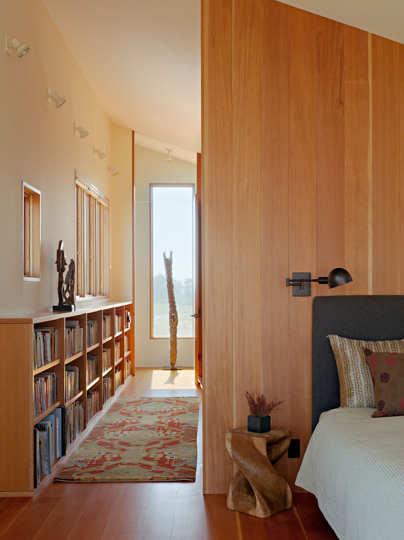 Wooden floors, shelving and walls have been used to create a sense of warmth in this bedroom.