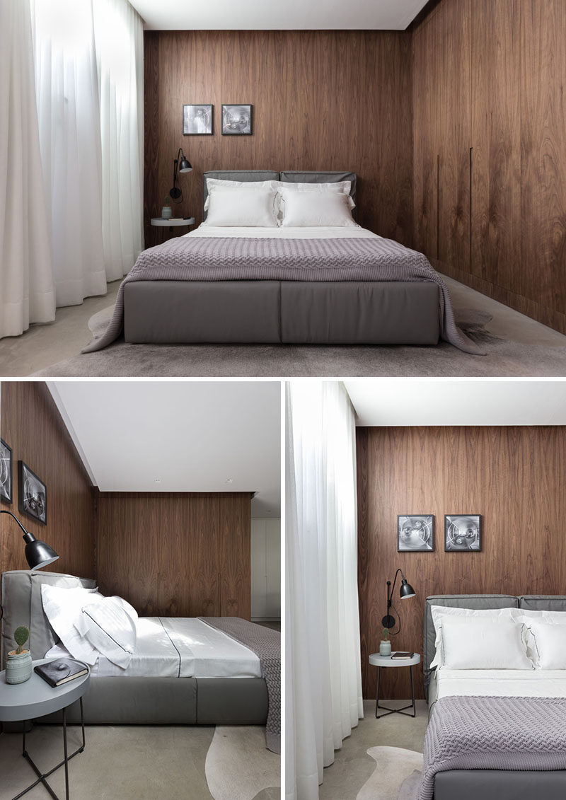 In this small apartment, dark wood helps to define the sleeping space, and a closet with a seamless appearance runs alongside the bed.