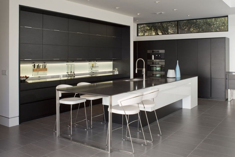The design of this kitchen has been kept minimal, with black cabinetry and a long island with space for informal dining.