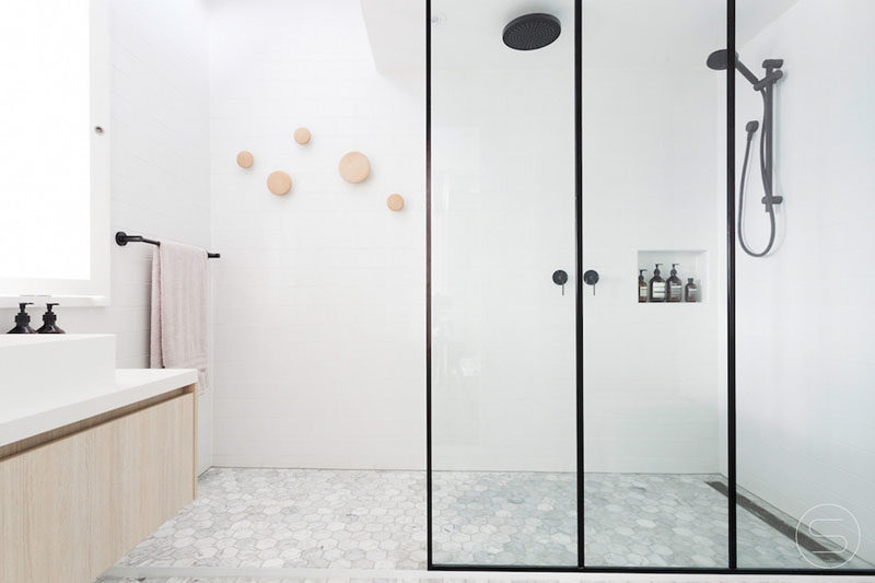 black frames surround the glass panels of this shower and match the hardware to create a modern looking bathroom with a lightdark contrast