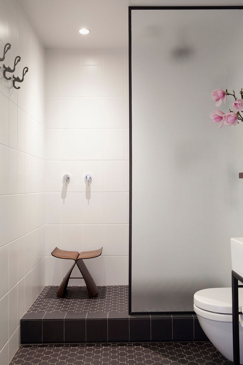 the black frame around the frosted glass door of this shower adds a simple sophistication to the space and ties together the other black elements in the