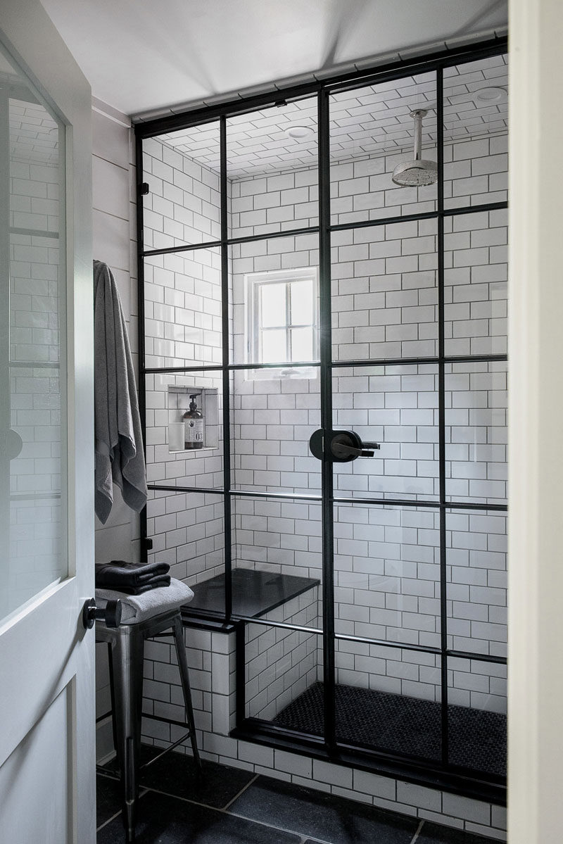 the black window like frame on the glass of this shower creates an industrial look in the bathroom and matches the small window pane on the opposite wall