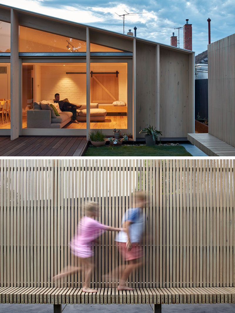 A wooden deck has been added to the back of this renovated house, and along one side of the yard is a wooden slat bench that also provides seating and privacy from the neighbors.