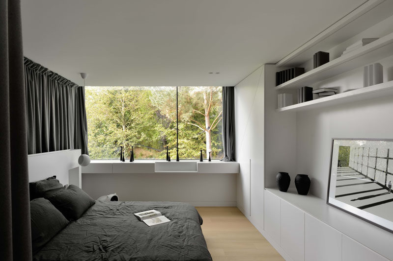 In this bedroom there's a wall covered in built-in cabinetry and open shelving.