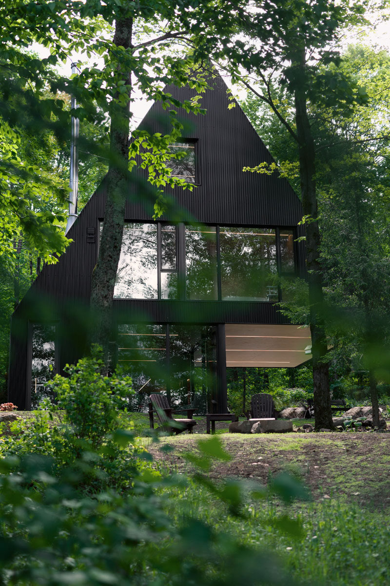 18 Modern House In The Forest // This black cabin is a summer home surrounded by a Hemlock forest in eastern Canada. #ModernHouse #ModernArchitecture #HouseInForest #HouseDesign