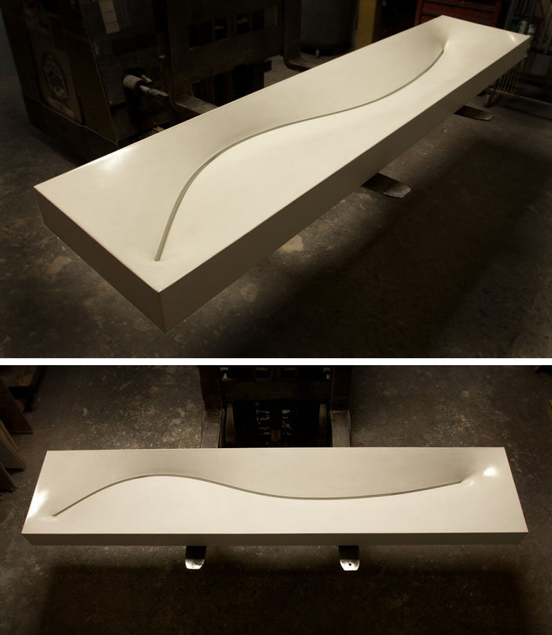 11 Creative Concrete Countertop Designs To Inspire You // A curved slot drain in this this long narrow sink gives it a smooth design and a creative drain alternative.