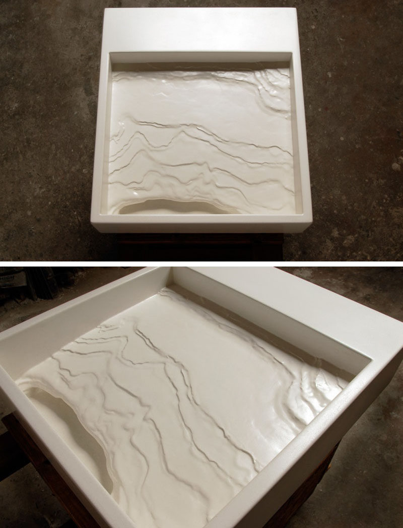 11 Creative Concrete Countertop Designs To Inspire You // This sink resembles an eroding shoreline that tilts down and sends water into a cave-like structure that then sends it down the hidden drain.