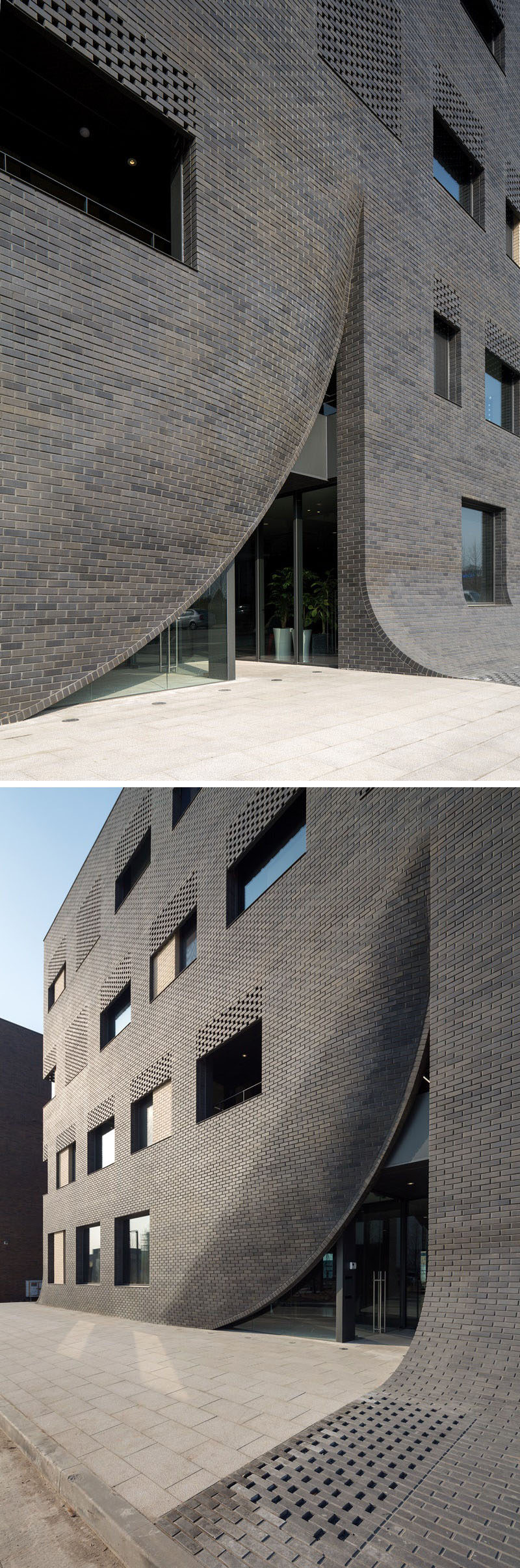 This black brick building in Korea has sections of curved brickwork that expose the entrances, and also curve down to meet the sidewalk.